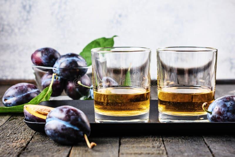 Plum alcoholic drink. Brandy Slivovica, and plum fruit stock photos