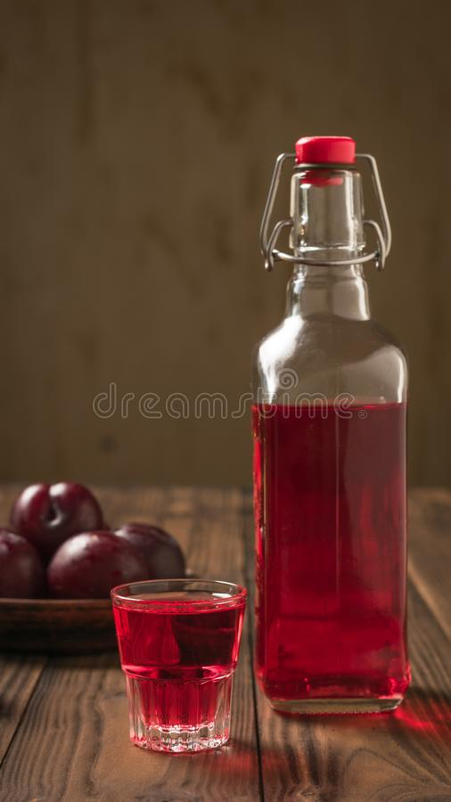 Plum alcoholic drink and plum berries on the rustic table. Flat lay. royalty free stock photos