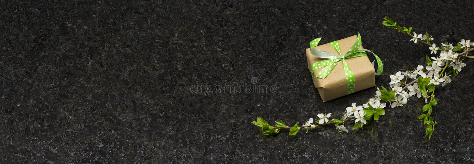 Plum blossom branch and gift box on Antique Brown granite countertop stock photos