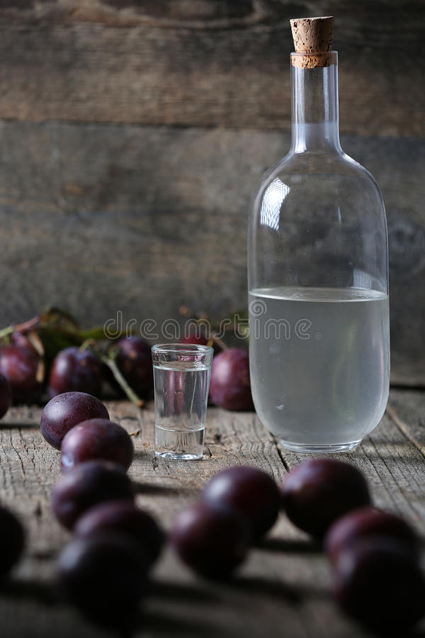 Plum brandy, bottle of Rakija. Plums brandy, Romanian tuica made of plums, wooden background stock photography