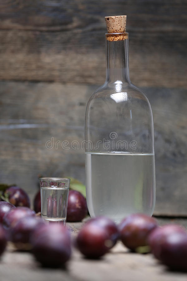 Plum brandy, bottle of Rakija. Plums brandy, Romanian tuica made of plums, wooden background stock images