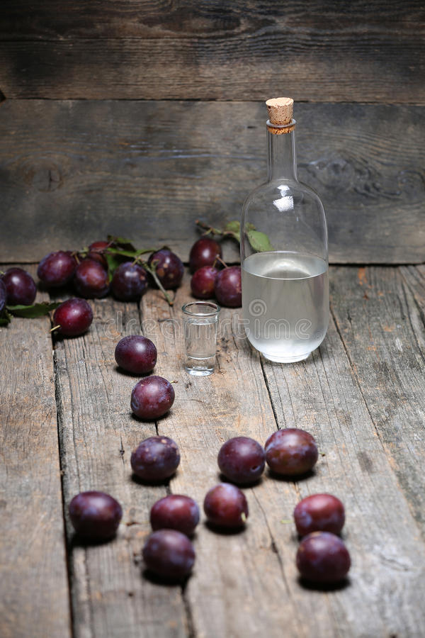 Plum brandy, bottle of Rakija. Plums brandy, Romanian tuica made of plums, wooden background royalty free stock photos