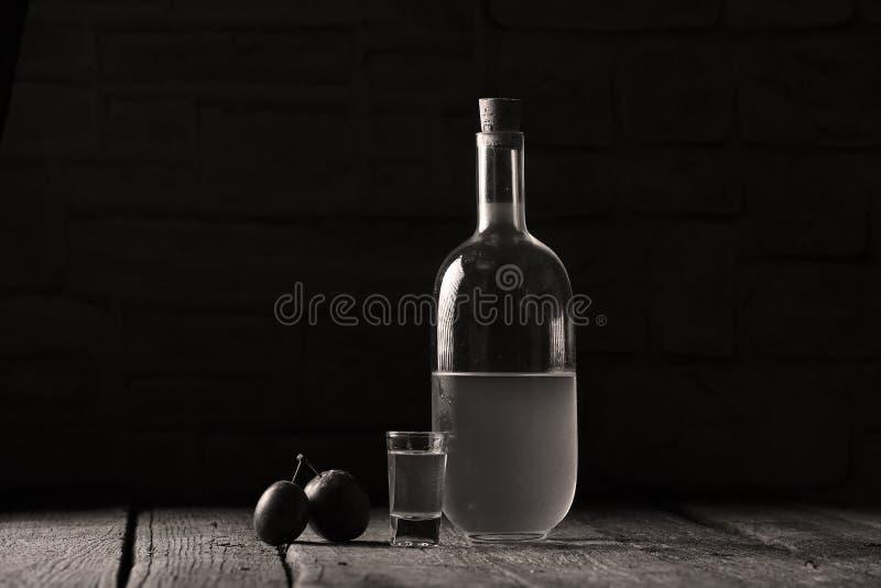 Plum brandy, bottle of Rakija. Plums brandy, Romanian tuica made of plums, wooden background stock image