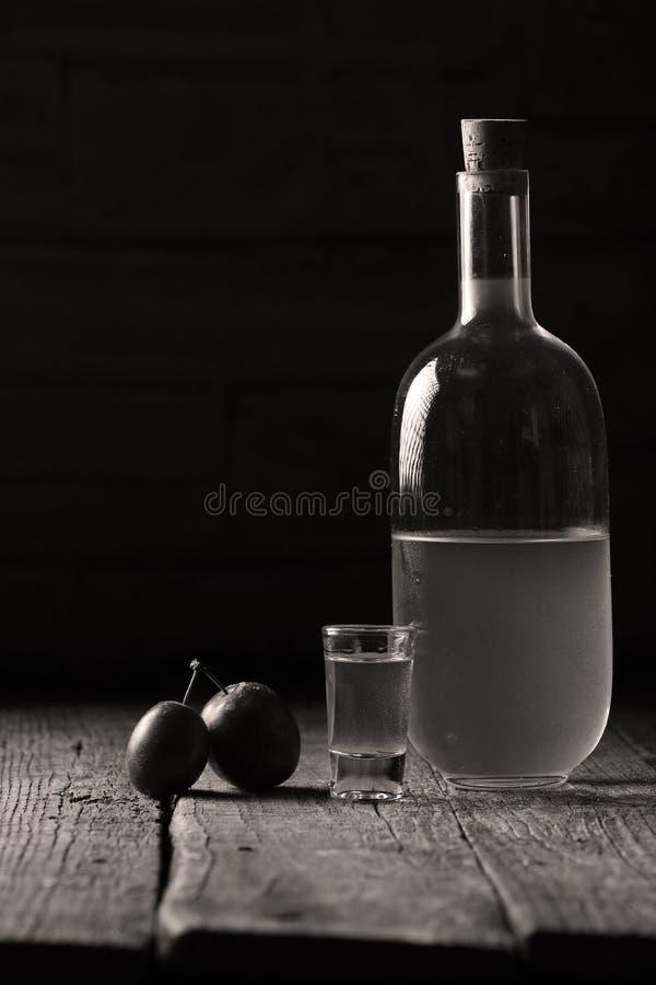 Plum brandy, bottle of Rakija. Plums brandy, Romanian tuica made of plums, wooden background royalty free stock image