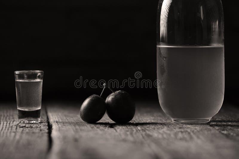 Plum brandy, bottle of Rakija. Plums brandy, Romanian tuica made of plums, wooden background royalty free stock images