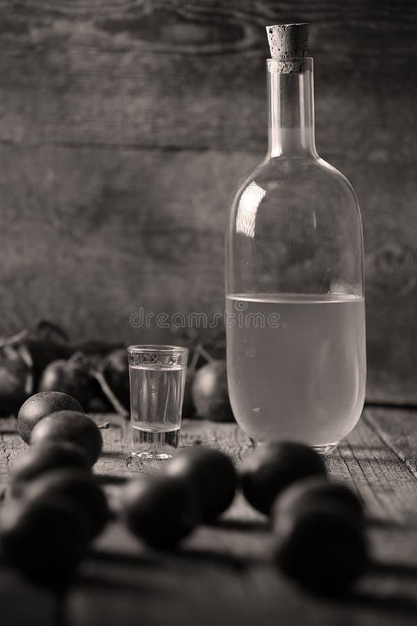 Plum brandy, bottle of Rakija. Plums brandy, Romanian tuica made of plums, wooden background royalty free stock photography