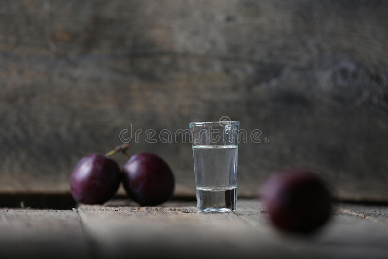 Plum brandy, glass of Rakija. Plums brandy, Romanian tuica made of plums, wooden background royalty free stock images
