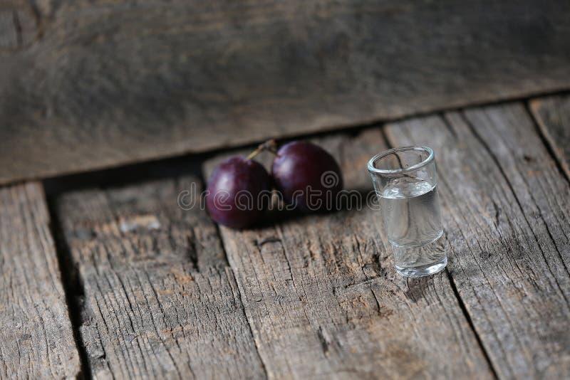 Plum brandy, glass of Rakija. Plums brandy, Romanian tuica made of plums, wooden background stock photography