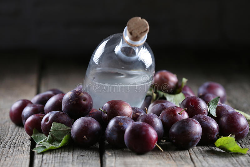 Plum brandy, Romanian tuica. Plums brandy, Romanian tuica made of plums, wooden background royalty free stock photography