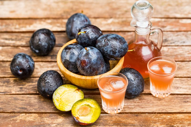 Plum brandy or slivovitz with fresh ripe plums. Close up plum liqueur or slivovitz, plum rakia with fresh and tasty plums in wooden bowl on wooden background royalty free stock photos