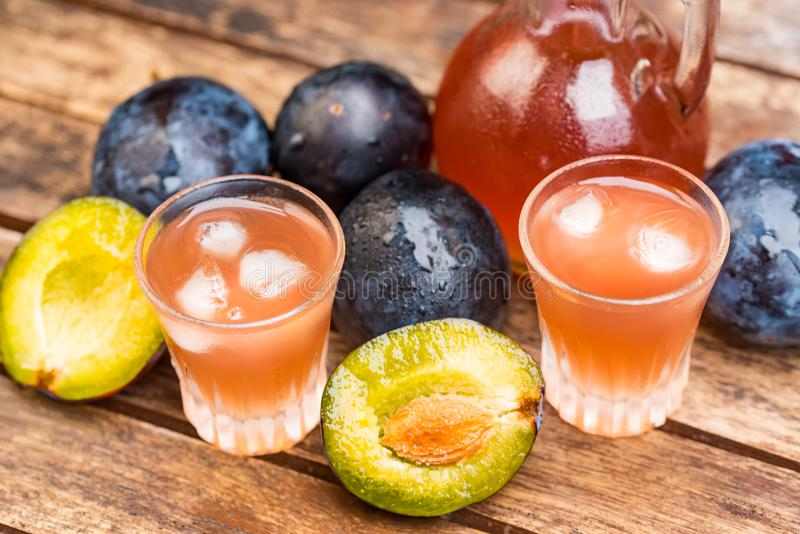 Plum brandy or slivovitz with fresh ripe plums. Close up plum liqueur or slivovitz, plum rakia with fresh and tasty plums in wooden bowl on wooden background stock photography