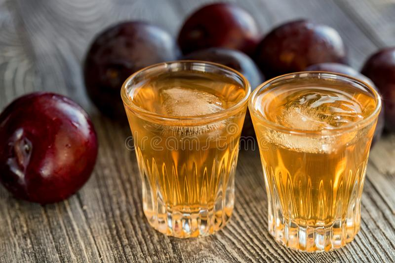 Plum brandy or slivovitz with fresh and tasty plum. Plum liqueur or slivovitz, plum rakia with fresh and tasty plum on rustic wooden background stock photography