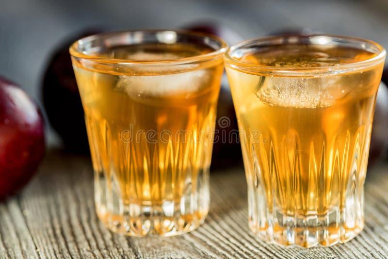 Plum brandy or slivovitz with fresh and tasty plum. Plum liqueur or slivovitz, plum rakia with fresh and tasty plum on rustic wooden background stock images