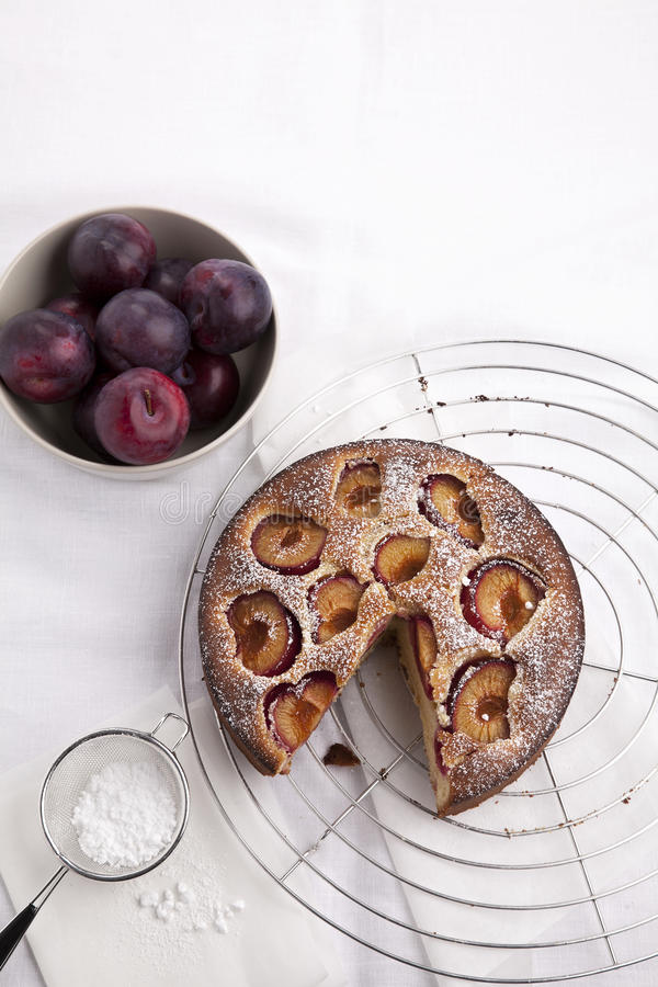 Plum cake. Picture of a plum cake with a bowl of plums and a sieve with powder sugar on a fabric stock image
