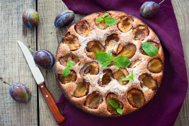 Plum cake over natural wood background. Plum cake and fresh plums over natural wood background stock photos