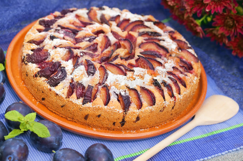 Plum cake. A whole plum cake on a blue table stock photo