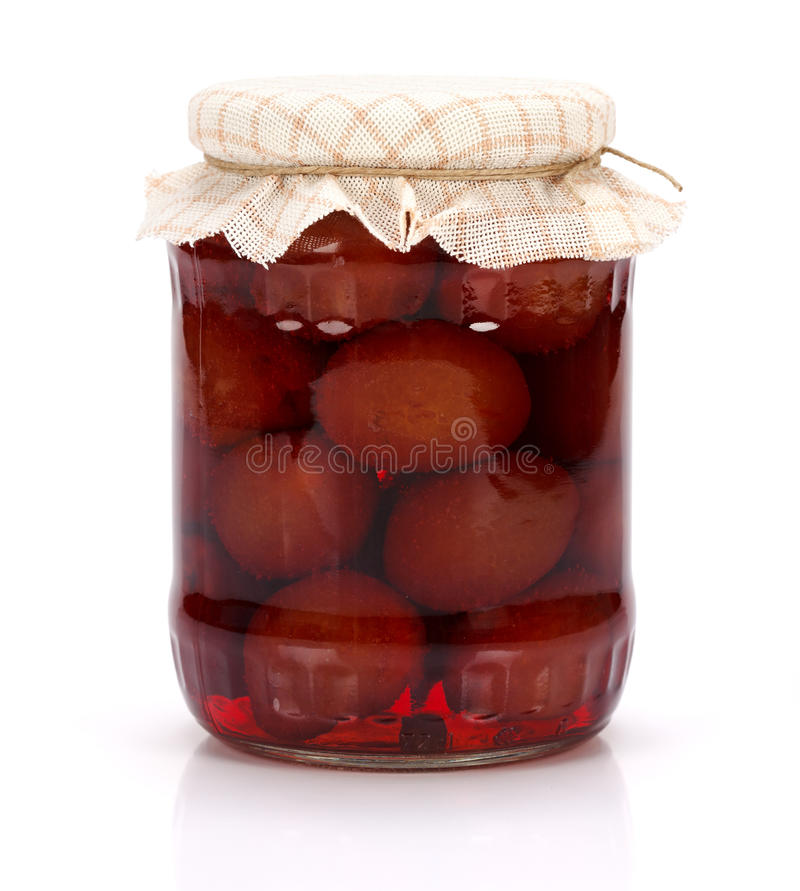 Plum compote. A jar of plum compote on white background royalty free stock photography