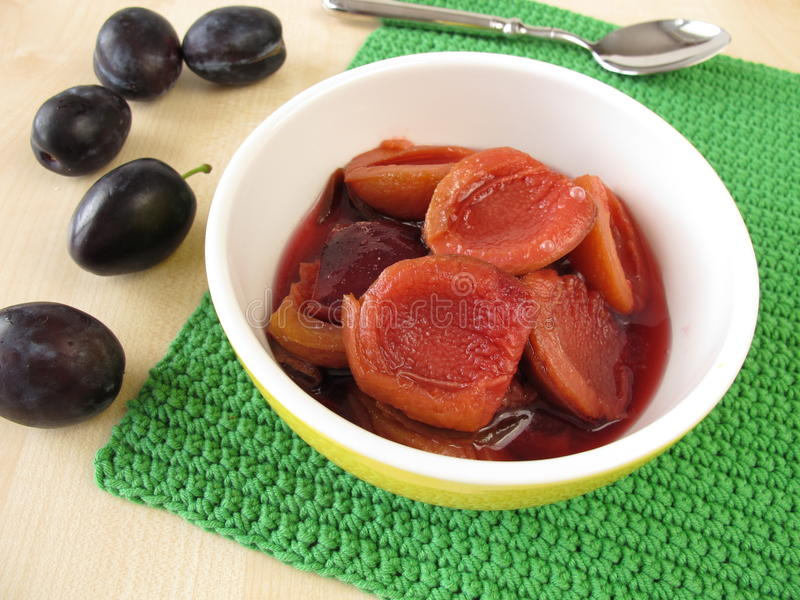 Plum compote. In bowl and fresh fruits stock photos