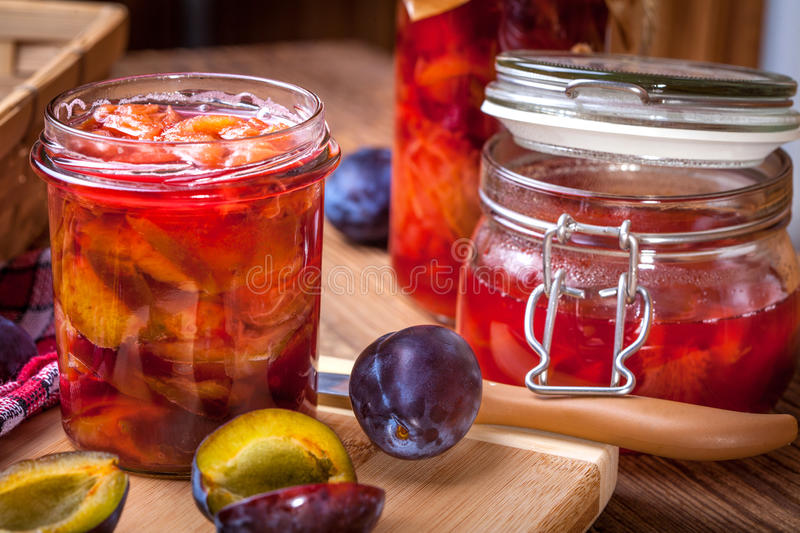 Plum compote. Plum compote with fresh fruit on a wooden table royalty free stock photography