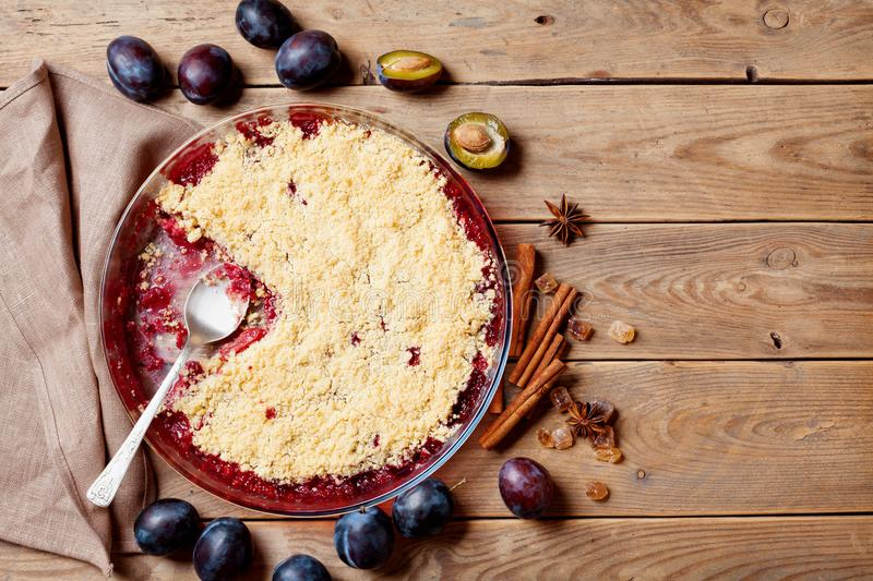 Plum crumble with aromatic spice on wooden rustic table top view. Autumn pastry. stock image