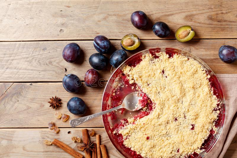 Plum crumble with aromatic spice on wooden rustic table top view. Autumn pastry dessert. stock photography