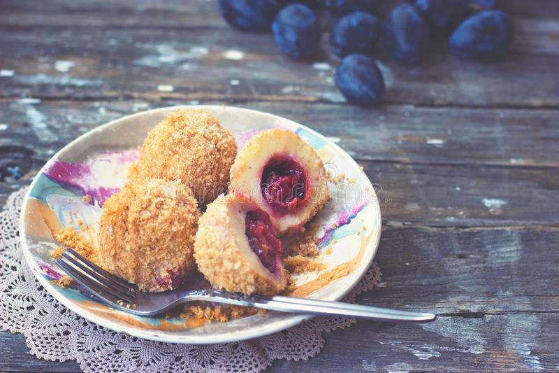 Plum dumplings, plums and plum sauce on wooden background royalty free stock photography