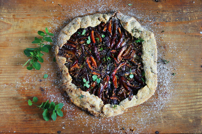 Plum galette pie with wine, almonds and marjoram stock photos