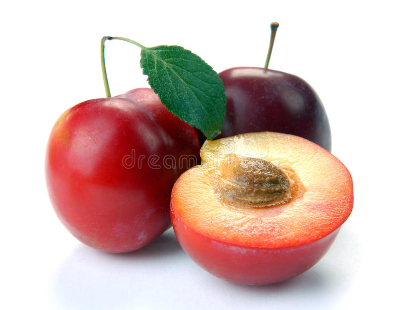 Plum and a half and leaves stock photography