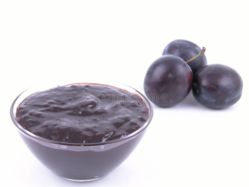 Plum jam. Bowl of plum jam and some fresh plums - isolated stock photo