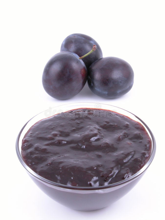 Plum jam. Bowl of plum jam and some fresh plums - isolated royalty free stock photos