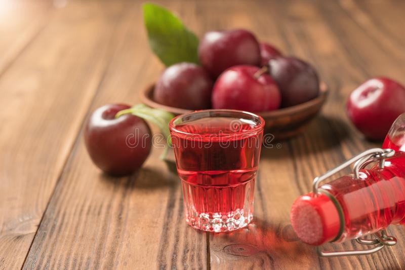 Plum liqueur in a glass and a bottle of fresh plums on a wooden table. Homemade alcoholic drink made from berries plum stock images