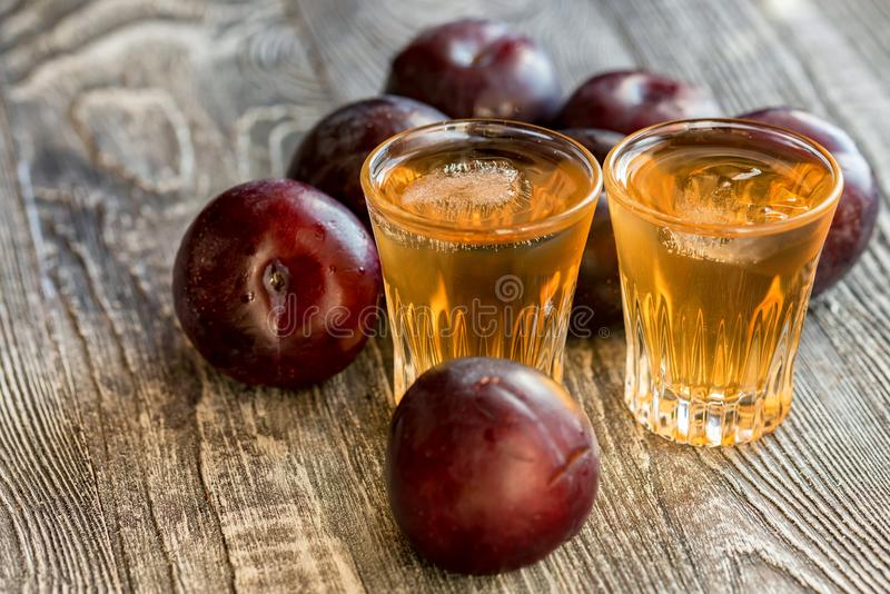Plum brandy or slivovitz with fresh and tasty plum. Plum liqueur or slivovitz, plum rakia with fresh and tasty plum on rustic wooden background royalty free stock photo