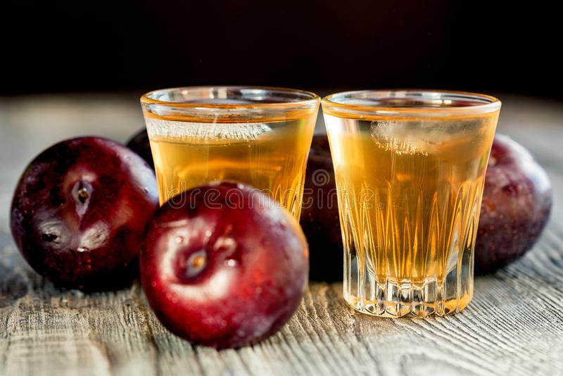 Plum brandy or slivovitz with fresh and tasty plum. Plum liqueur or slivovitz, plum rakia with fresh and tasty plum on rustic wooden background royalty free stock images