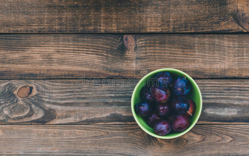 Plum In Plate. Old metal plate with plums over dark board. Top view. Fruits background with space for text. Agriculture, Gardening, Harvest Concept.n royalty free stock photography