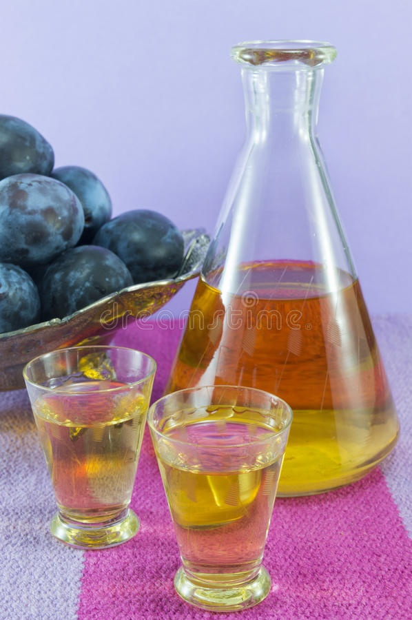 Plum schnapps and fresh plums stock images