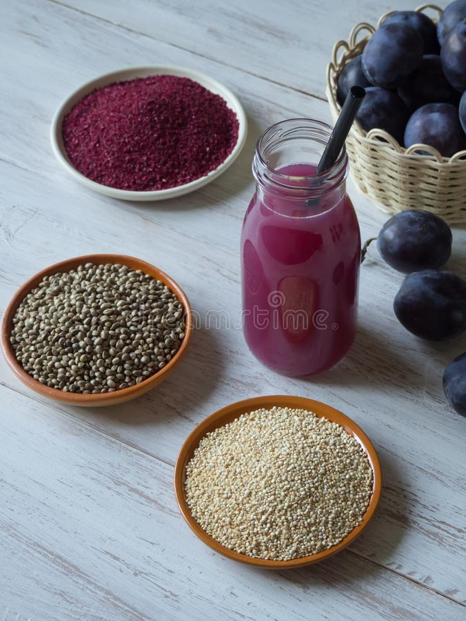 Plum smoothie with Superfoods on a white wooden table. Healthy food with supplements. royalty free stock image