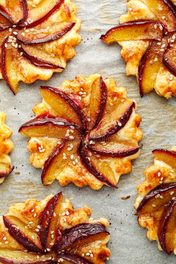 Plum tarts, fruit pastries with cinnamon on a white background, delicious dessert with puff pastry and fruits. Top view stock photography