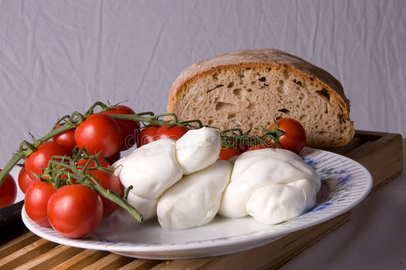 Plum Tomatoes and Mozzarella. Ingredients to make a simple salad called caprese. Fresh mozzarella and plum tomatoes are arranged on a white plate with a sliced stock photo