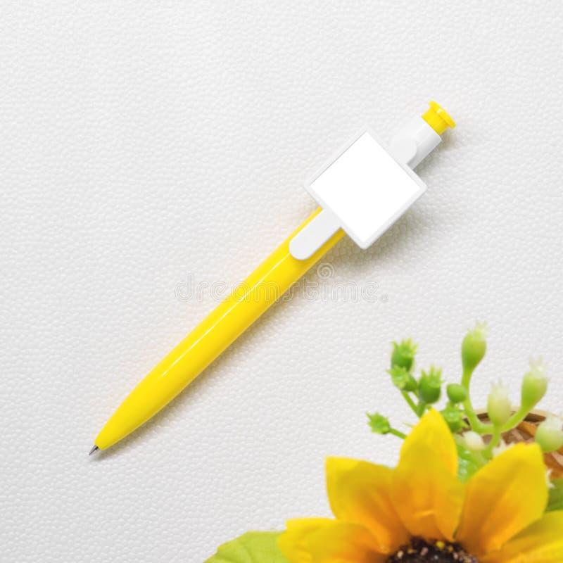 Pluma amarilla en el fondo de cuero blanco Bolígrafo en blanco para su diseño fotos de archivo