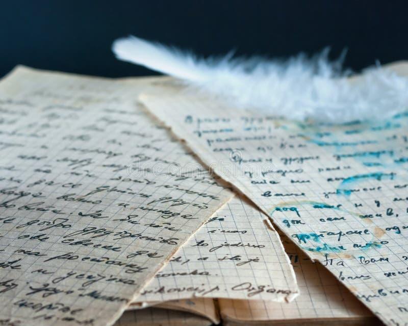 Pluma blanca en viejos documentos imágenes de archivo libres de regalías