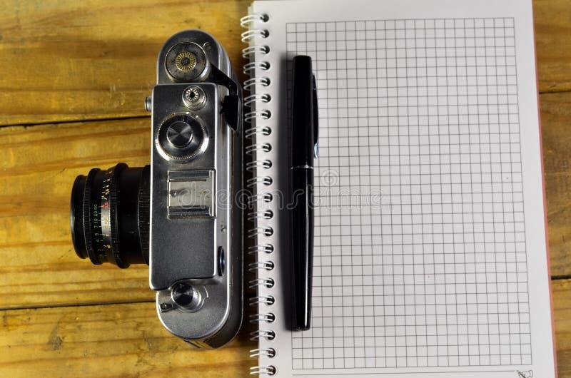 Pluma, cámara vieja, y cuaderno en la tabla de madera fotos de archivo libres de regalías
