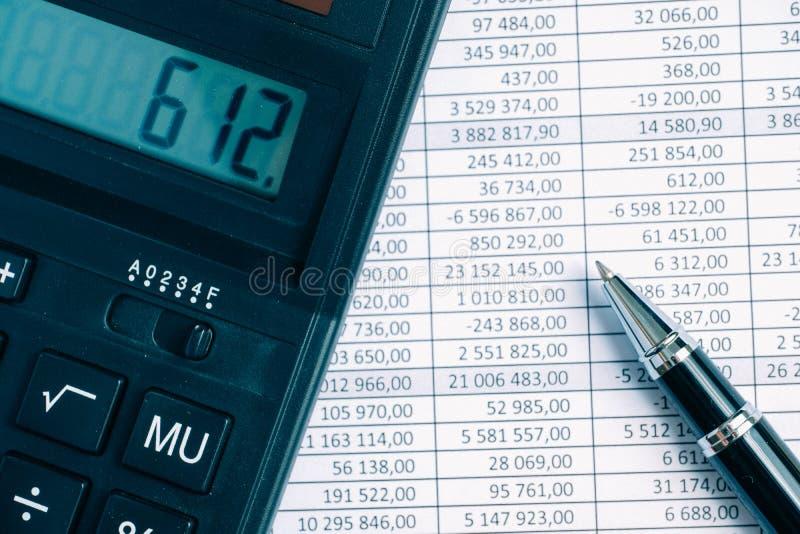 Pluma con la calculadora en el fondo de papel con totales fotografía de archivo libre de regalías