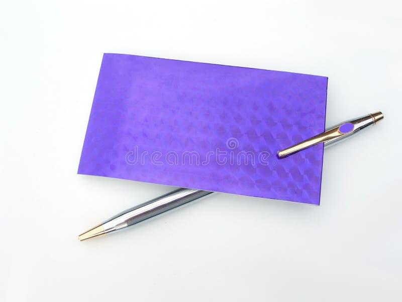 Pluma con la tarjeta púrpura foto de archivo