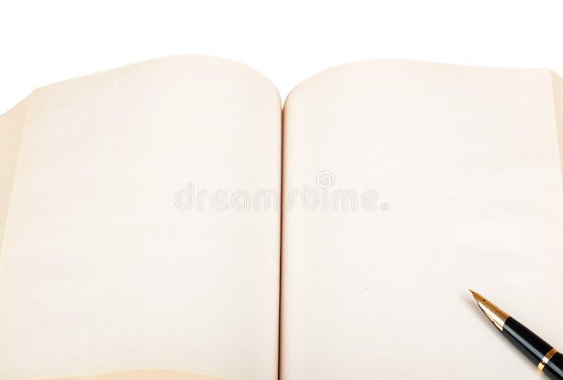 La pluma miente en un libro abierto imagenes de archivo