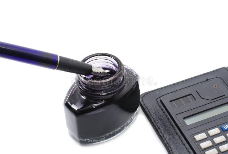 Pluma de la escuela vieja con la calculadora y la tinta en la botella fotos de archivo libres de regalías