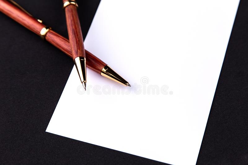 Pluma de lujo y l?piz mec?nico en madera y oro con una hoja de papel blanca fotografía de archivo