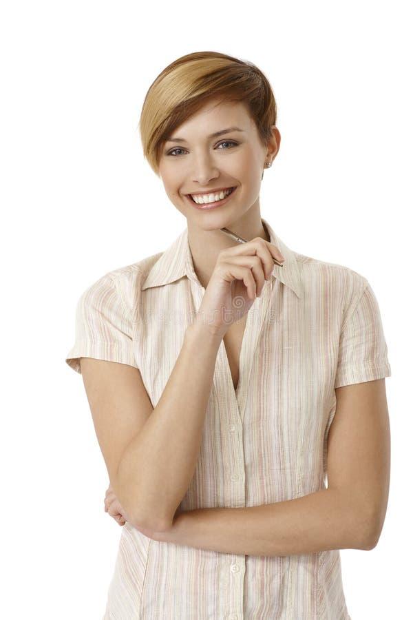 Pluma de tenencia atractiva de la mujer joven foto de archivo