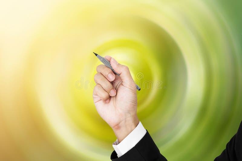 Pluma de tenencia del hombre de negocios en la posición de la escritura, con el fondo radial espiral verde fotos de archivo libres de regalías