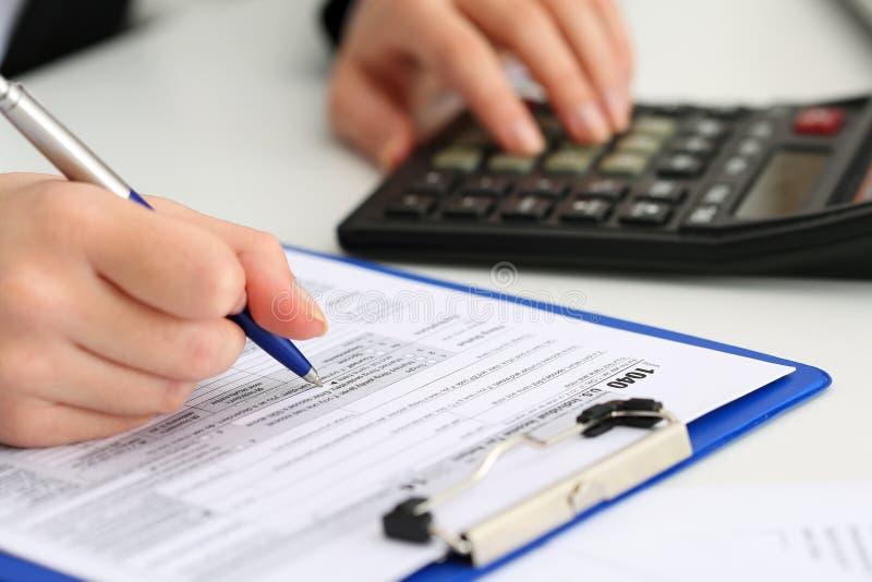 Pluma de tenencia femenina de la mano del contable que cuenta en la calculadora fotografía de archivo libre de regalías