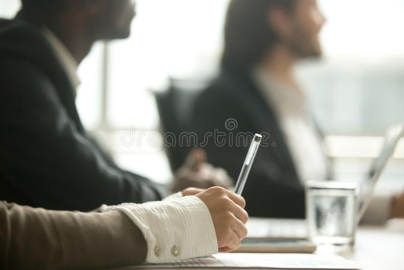 Pluma de tenencia femenina de la mano que hace notas en la reunión, opinión del primer fotografía de archivo libre de regalías